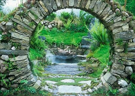 A moon gate archway made out of dry stone walling. Small pond in centre with natural stone seats around edge.